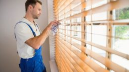 33949768 - handyman cleaning blinds with a towel in a new house