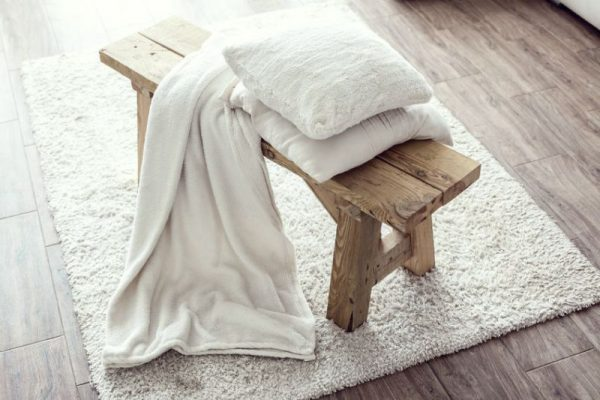 47181969 - still life details, stack of white cushions and blanket on rustic bench on white carpet