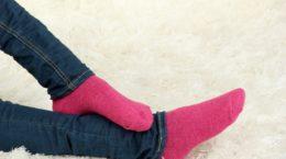 16739876 - female legs in colorful socks on  white carpet background