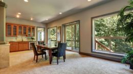 61713917 - open floor plan dining room with view of kitchen cabinetry. beige carpet floor and opened glass sliding doors to balcony. northwest, usa