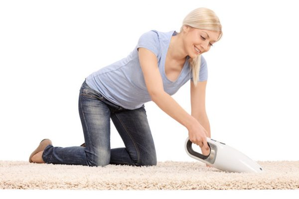 39282218 - young  blond woman cleaning a carpet with a handheld vacuum cleaner isolated on white background