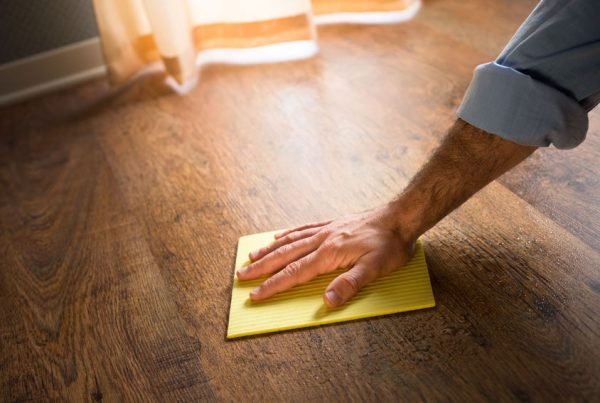 32522140 - male hand cleaning and rubbing an hardwood floor with a microfiber cloth.